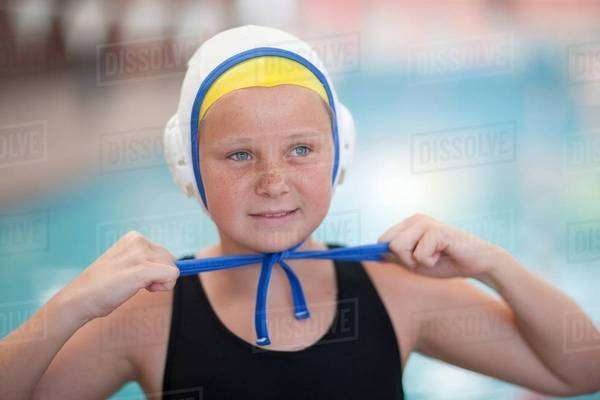 Portrait of schoolgirl water polo player fastening swimming cap Royalty-free stock photo