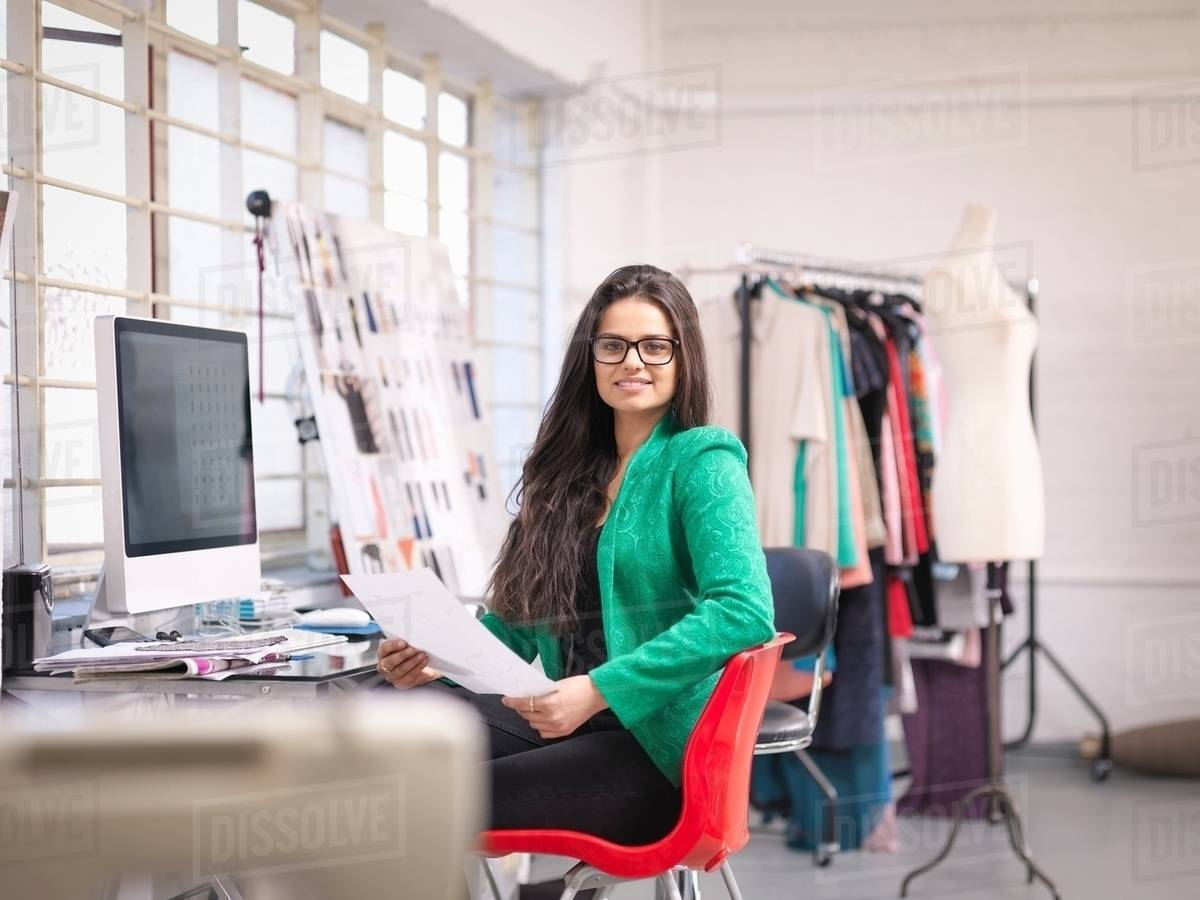 Fashion Designer Working At Computer In Fashion Design Studio Portrait Stock Photo Dissolve