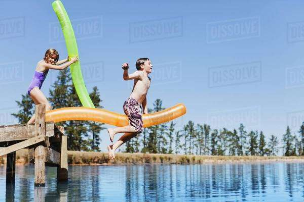 Children jumping into lake from jetty Royalty-free stock photo