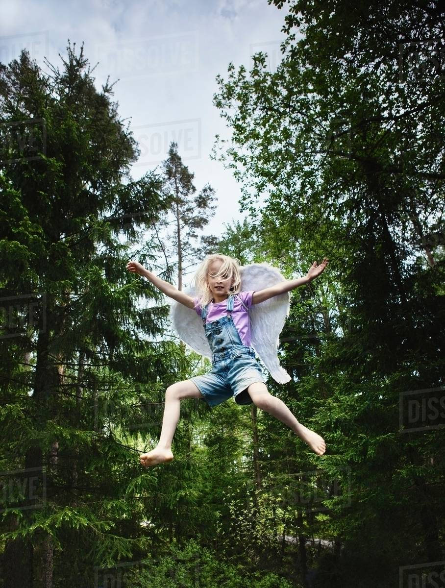 Girl wearing wings and jumping in forest Royalty-free stock photo