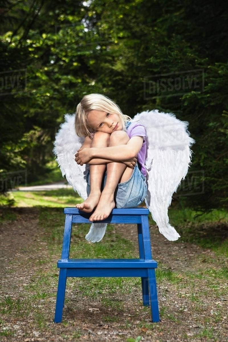 Bored girl in wings sitting on stool Royalty-free stock photo
