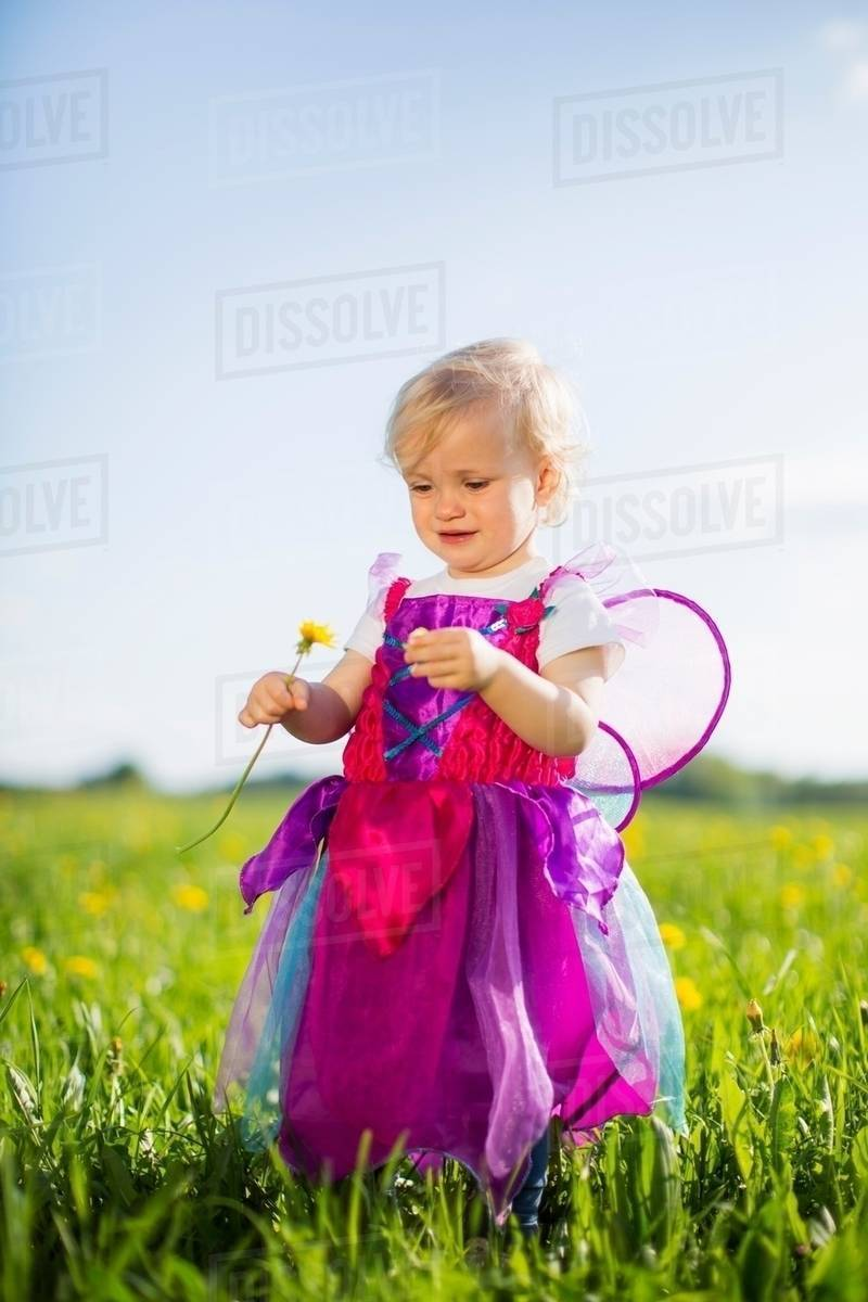 Girl in fairy costume playing in field Royalty-free stock photo