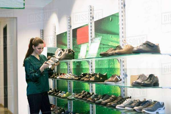 Young female customer selecting sandal in shoe shop Royalty-free stock photo