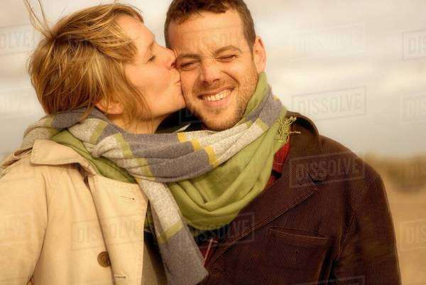 Woman kissing man on beach scarves mixed Royalty-free stock photo
