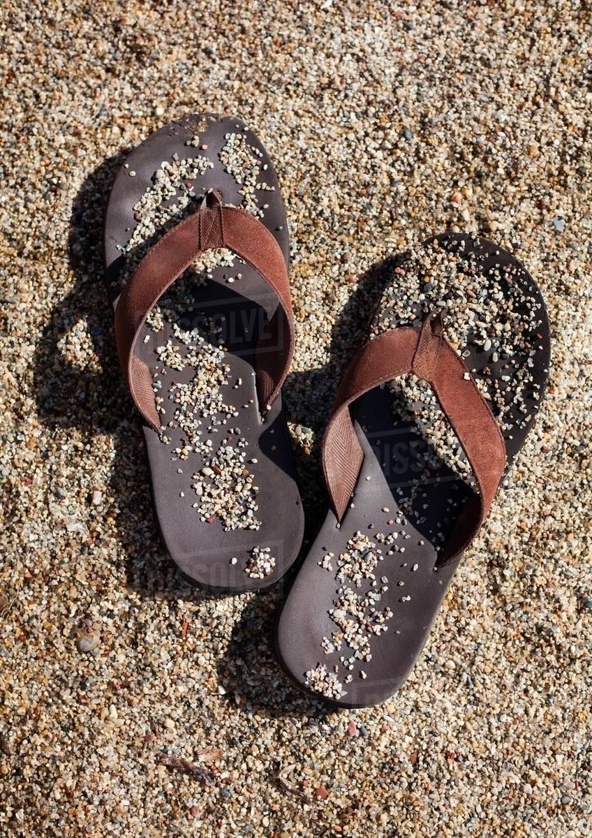 c56429fb1 Sandy flip flops on beach - Stock Photo - Dissolve