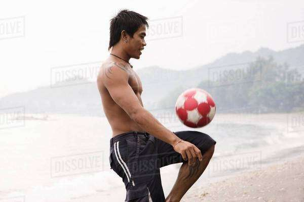 Guy playing football on beach Royalty-free stock photo