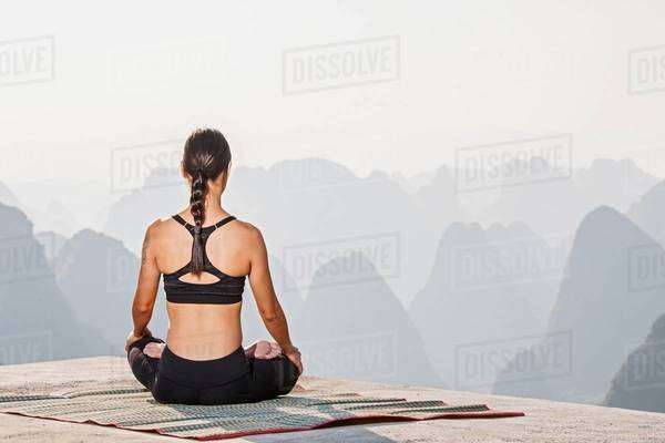 Rear view of woman in yoga lotus pose above limestone mountains, Yangshuo, Guangxi Zhuang, China Royalty-free stock photo