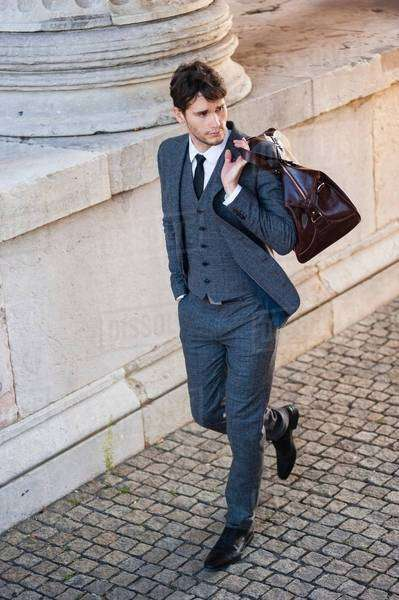 High angle view of mid adult man wearing full suit carrying bag over shoulder looking away Royalty-free stock photo
