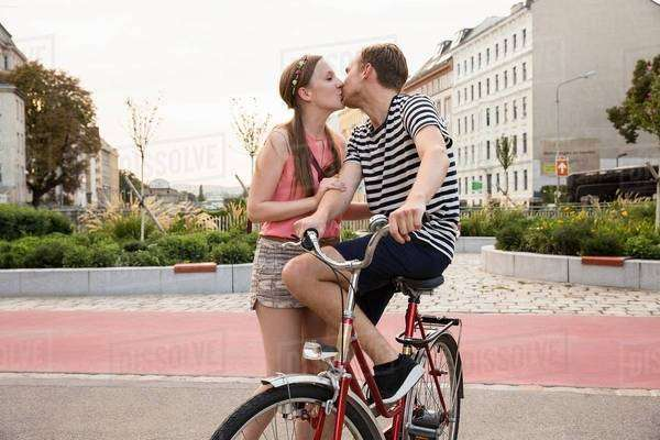 Young man sitting on bicycle kissing young woman Royalty-free stock photo