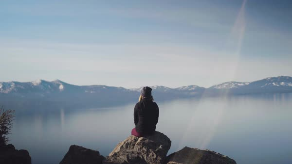A young woman sitting on a boulder high above a mountain lake spreads her arms with joy and makes a peace sign with her hands Royalty-free stock video