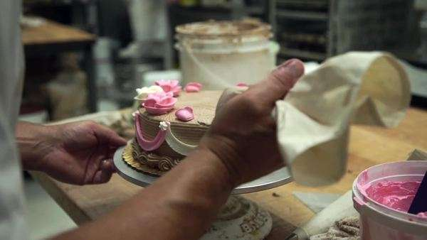 Slow motion of a baker decorating a cake Royalty-free stock video