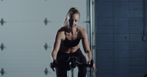 Medium wide shot of a woman riding a spin bike Royalty-free stock video