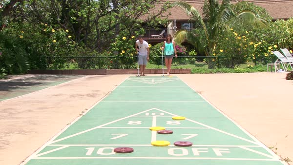 Model released man and woman playing shuffleboard outside on sunny day in Maui Hawaii, real time. Royalty-free stock video