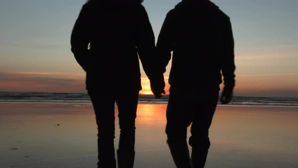 Two love birds walk out holding hands on sandy beach and get close for a sunset kiss. Royalty-free stock video