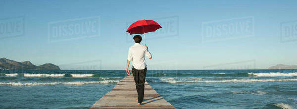 Man walking on pier with umbrella, rear view Royalty-free stock photo