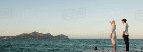 Couple standing on pier looking at view Royalty-free stock photo