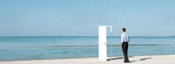 Businessman walking on beach towards open door, rear view Royalty-free stock photo