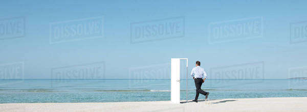 Man running on beach towards open door, rear view Royalty-free stock photo