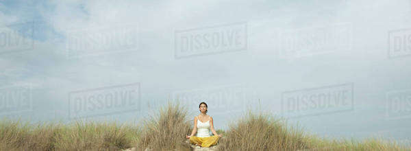 Mature woman meditating on beach Royalty-free stock photo