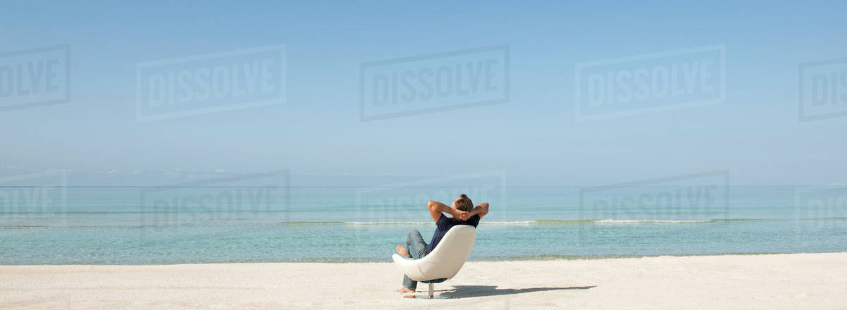 Man Relaxing In Chair On Beach Rear View