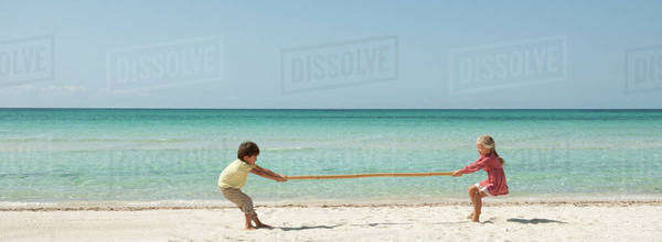 Children playing tug-of-war with bamboo at the beach Royalty-free stock photo