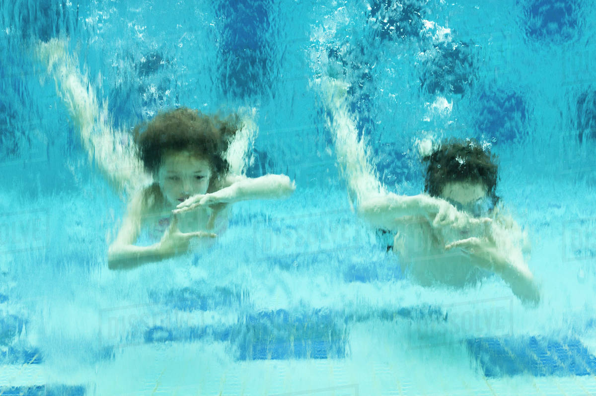 Brother and sister swimming underwater in swimming pool, hands ...