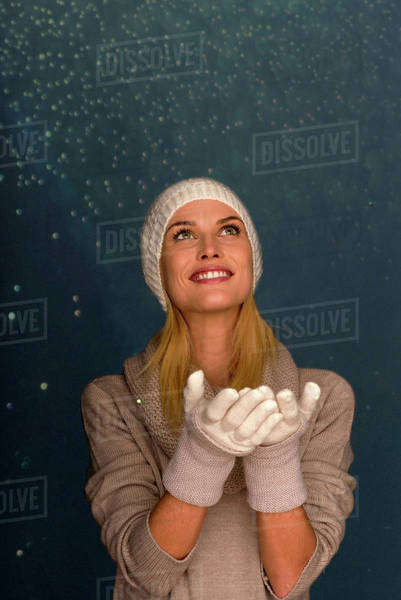 Woman wearing knit hat and gloves in front of snowy background, portrait Royalty-free stock photo