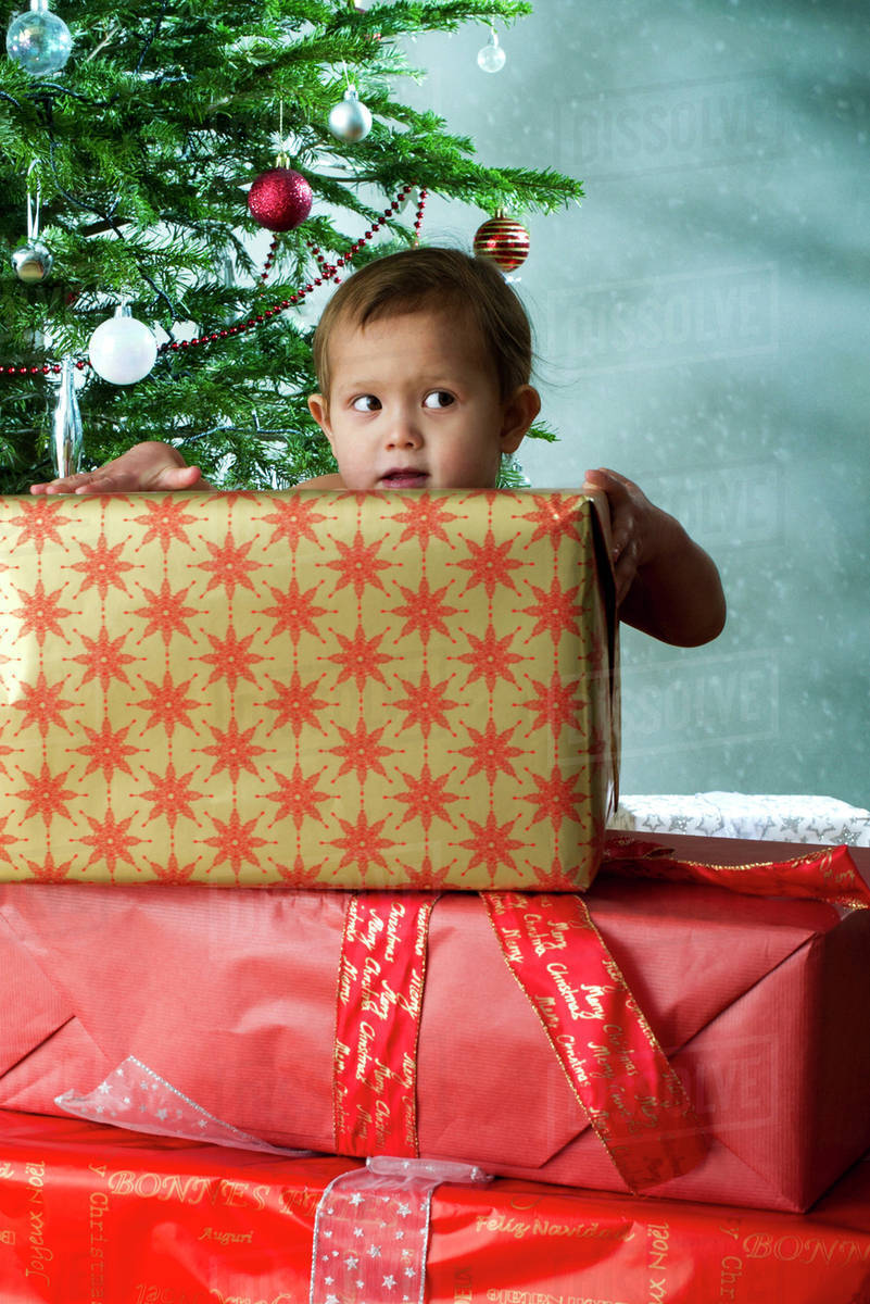 baby girl standing behind stack of christmas gifts with mischievous expression
