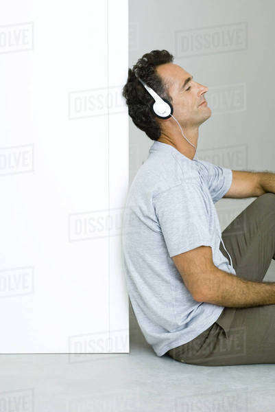 Man sitting on the ground, listening to headphones, eyes closed Royalty-free stock photo