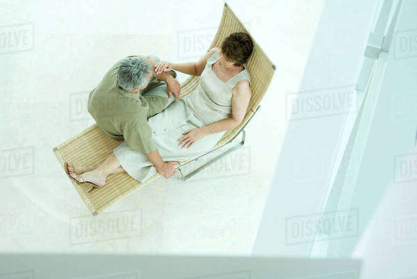 Mature couple sitting together on lounge chair, high angle view Royalty-free stock photo