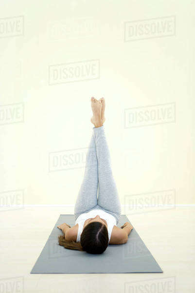 Woman lying on back with legs raised in the air Royalty-free stock photo