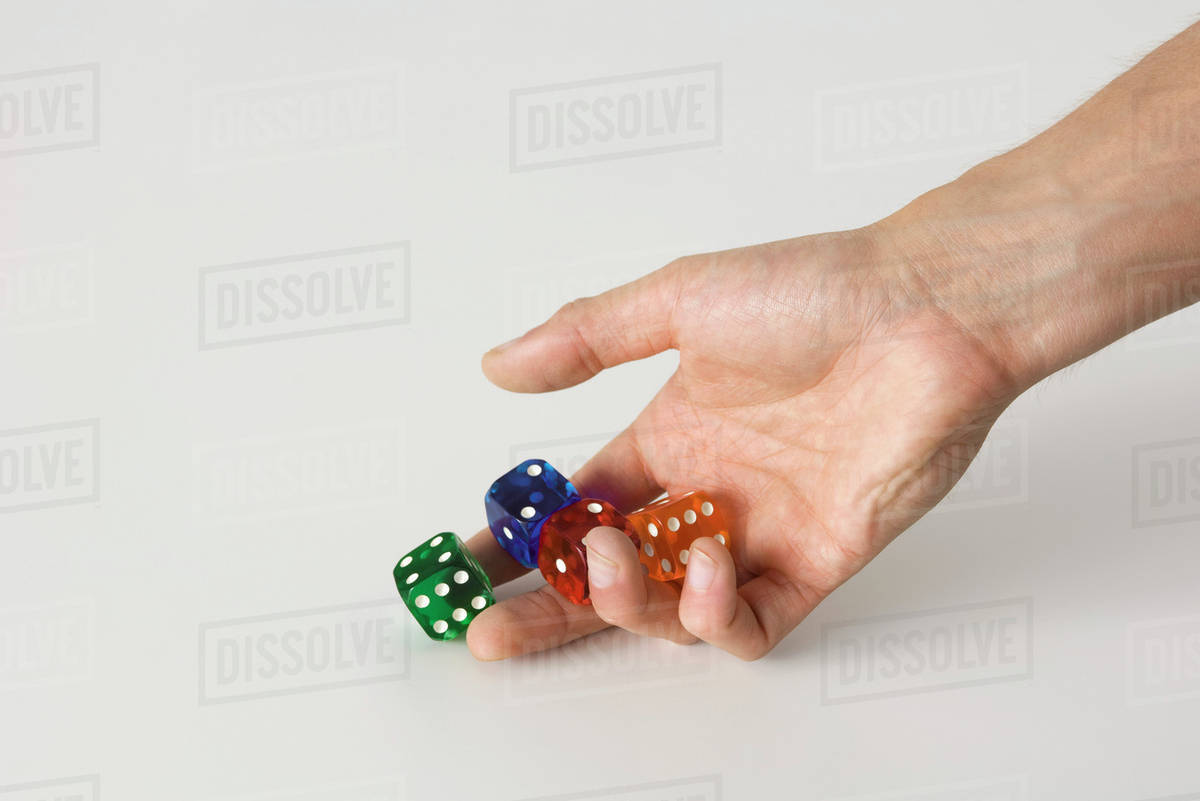 Hand rolling dice stock photo
