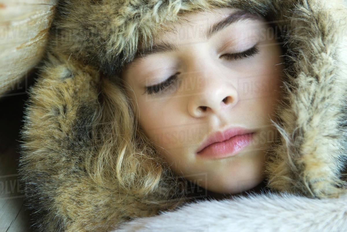 Preteen Girl Wearing Fur Hat Wrapped In Fur Blanket Sleeping Close Up Portrait Stock Photo