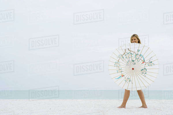 Woman walking behind parasol at the beach, smiling at camera Royalty-free stock photo