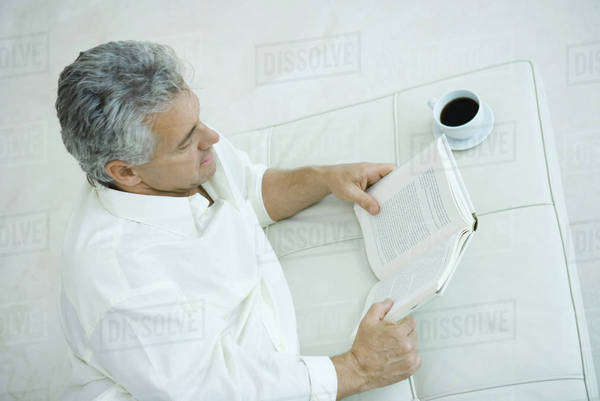 Mature man lying on side next to coffee cup, reading book, high angle view Royalty-free stock photo
