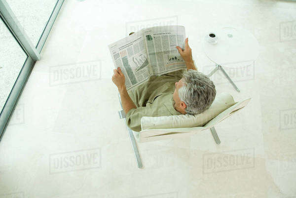 Man sitting, reading newspaper, high angle view Royalty-free stock photo