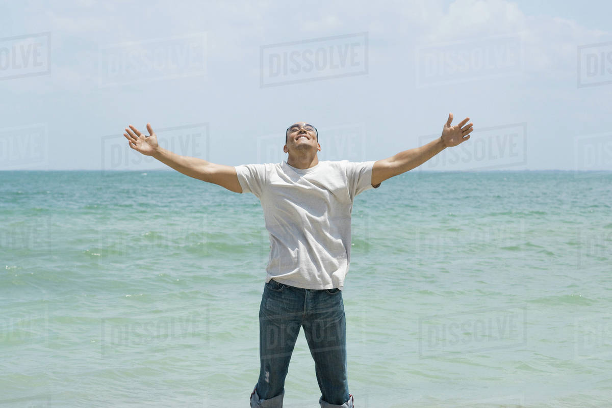 man standing by the sea with arms outstretched head back smiling