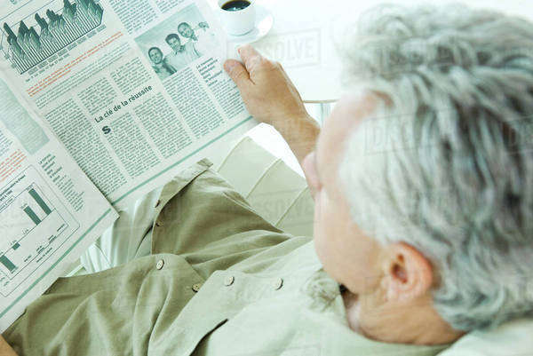Mature man reading newspaper, over the shoulder view Royalty-free stock photo