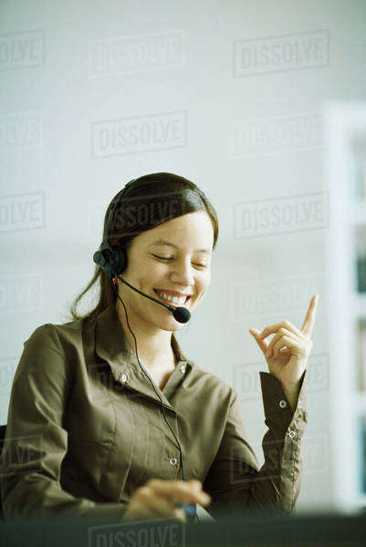 Woman wearing headset, index finger raised, smiling, looking down Royalty-free stock photo