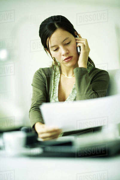 Woman using cell phone, looking down at document, selective focus Royalty-free stock photo