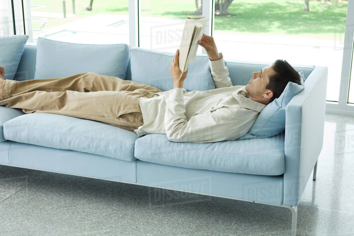 Man Lying On Sofa Reading Book Side View