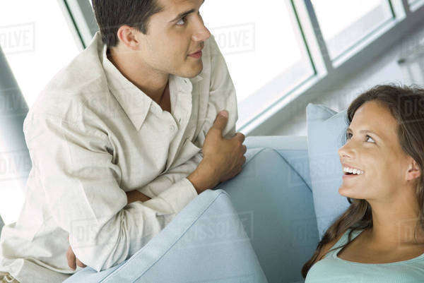 Young couple chatting together, female lying on couch, both smiling Royalty-free stock photo