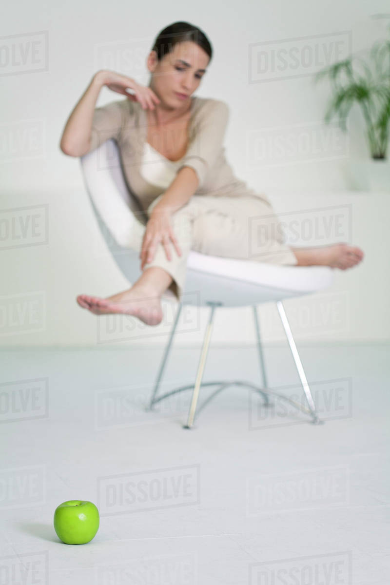Woman Relaxing In Chair Looking At Le On Floor Foreground