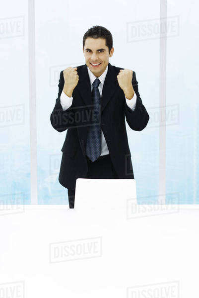 Businessman standing with fists up, smiling at camera Royalty-free stock photo