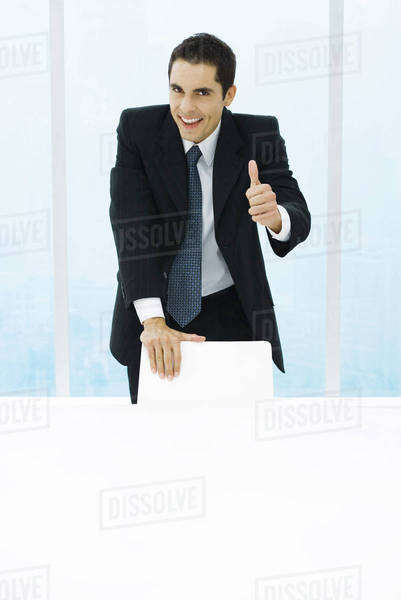 Businessman leaning on back of chair, giving thumbs up to camera Royalty-free stock photo