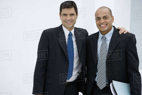 Two businessman, one with arm around the other's shoulder, smiling at camera Royalty-free stock photo