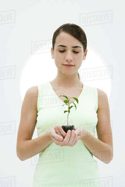 Woman holding potted seedling, looking down Royalty-free stock photo