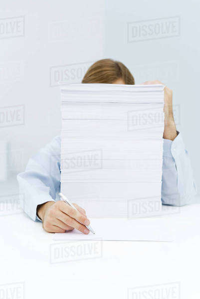 Man hiding behind tall stack of paper, reaching around to write on a single sheet of paper Royalty-free stock photo