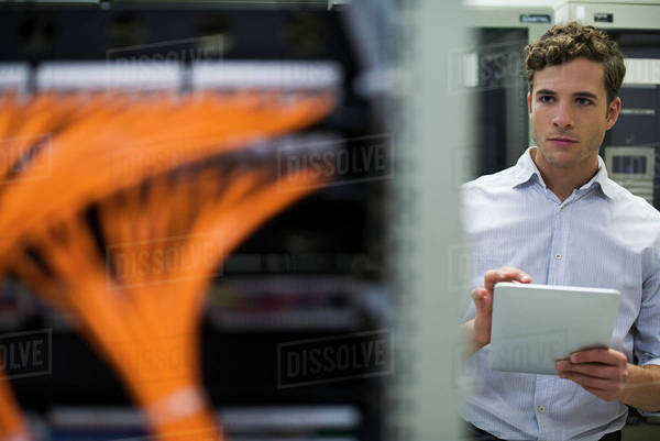 Computer technician using digital tablet performing maintenance check of mainframe equipment Royalty-free stock photo