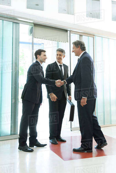 Businessman meeting associates in office lobby Royalty-free stock photo